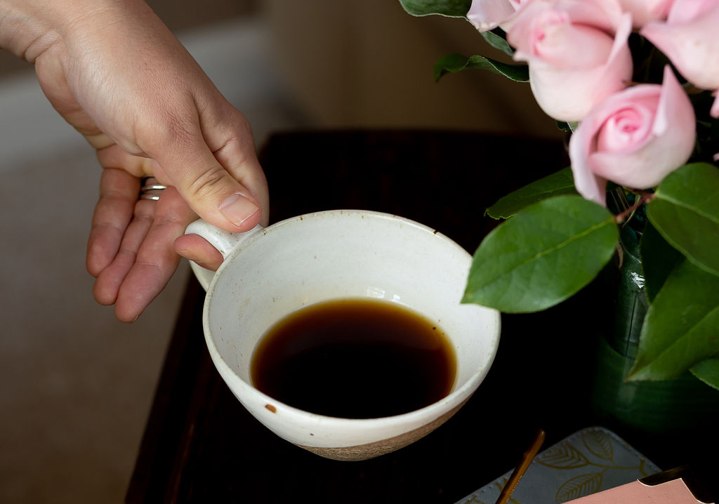 Hand holding a cup of coffee with pink roses on a table. Photo by Melanie Grizzel Photographyl